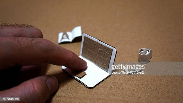 Cropped Hand Touching Of Artificial Laptop With Book And Cell Phone On Table