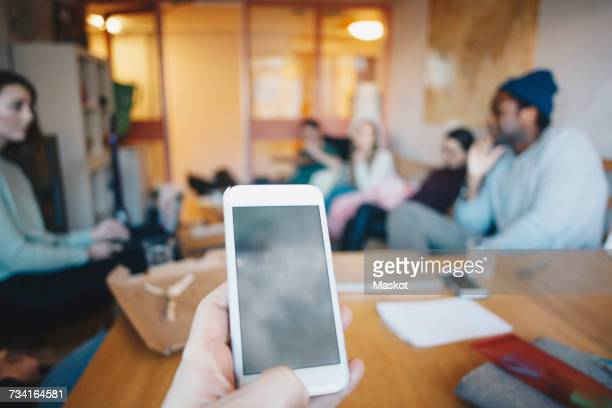 Cropped hand woman using mobile phone against friends in college dorm room