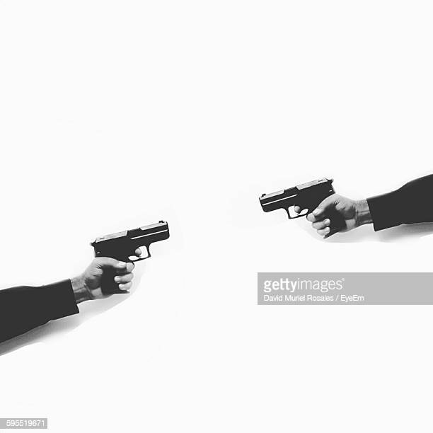 Cropped Hands Holding Handguns Against White Background