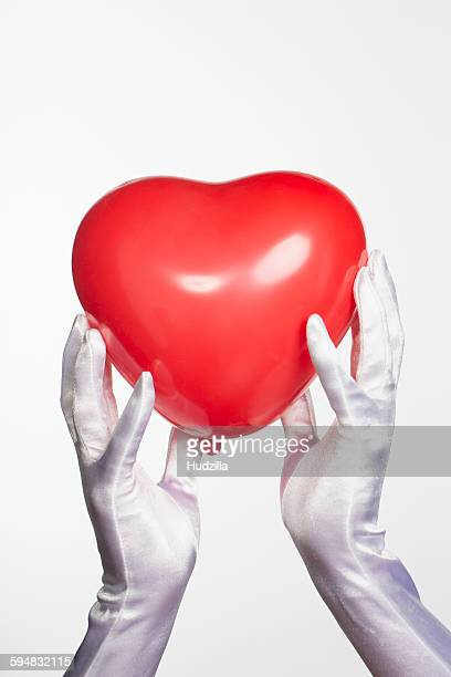 Cropped hands of bride holding heart shape balloon against white background