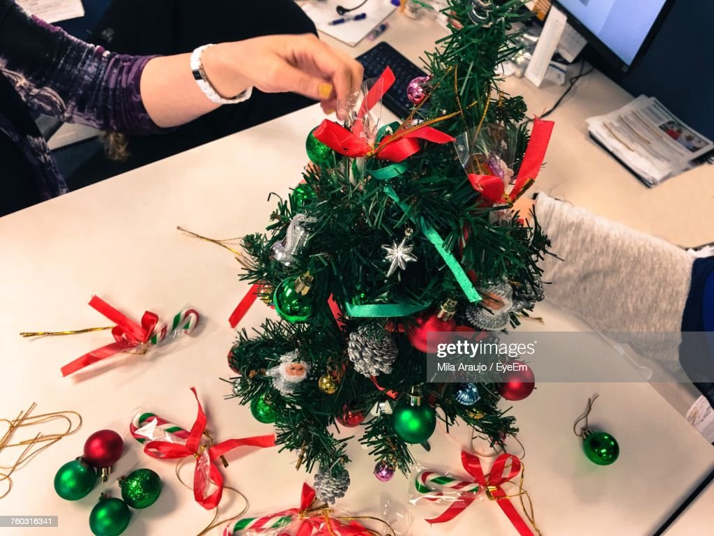 cropped hands of business people decorating christmas tree at table in office - People Decorating A Christmas Tree