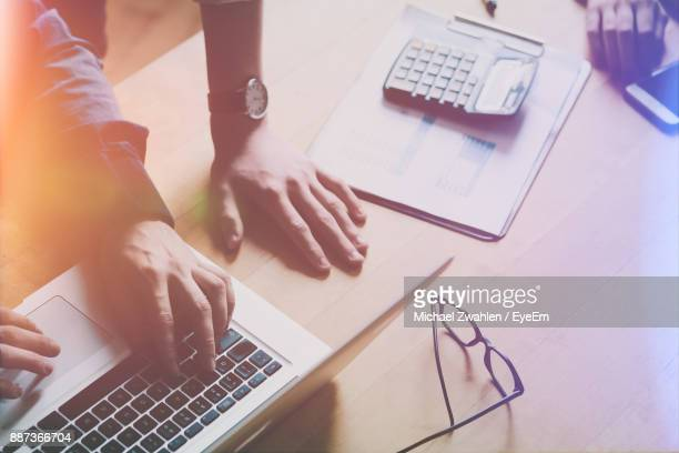 Cropped Hands Of Business People Discussing Over Laptop In Office