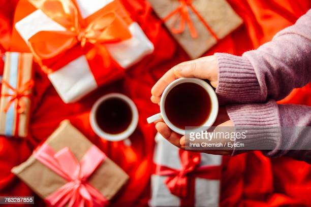 Cropped Hands Of Child Holding Coffee Cup By Gifts On Bed