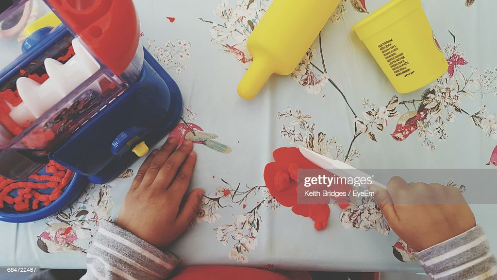 Cropped Hands Of Child Playing With Clay On Table At Home