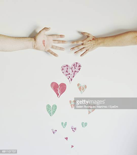 Cropped Hands Of Couple Against Broken Hearts Graffiti On White Wall