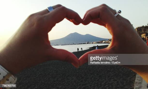 Cropped Hands Of Couple Making Heart Shape At Sandy Beach