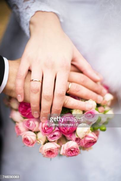 Cropped Hands Of Couple On Bouquet At Wedding Ceremony