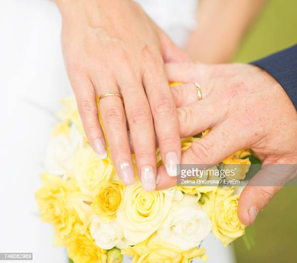 Cropped Hands Of Couple On Yellow Roses At Wedding Ceremony