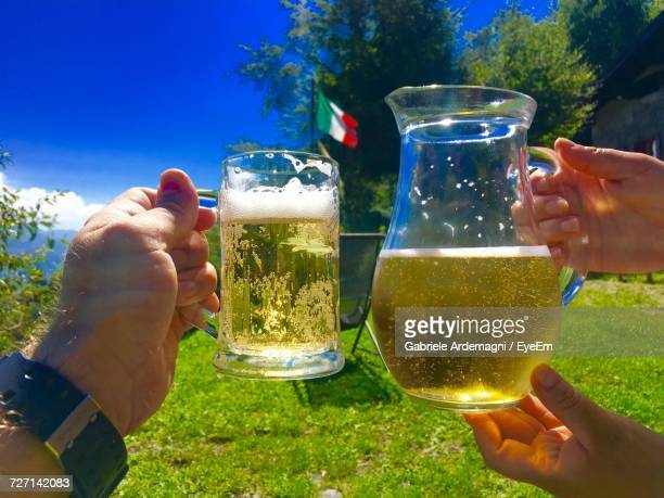 Cropped Hands Of Friends Toasting Beer Against Italian Flag On Grassy Field
