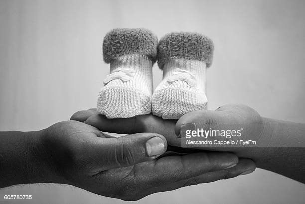 Cropped Hands Of Man And Woman With Baby Booties Against Wall