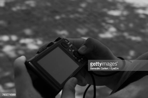 Cropped Hands Of Man Holding Camera While Standing On Street