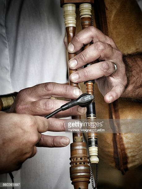 Cropped Hands Of Man Playing Bagpipe While Person Holding Microphone