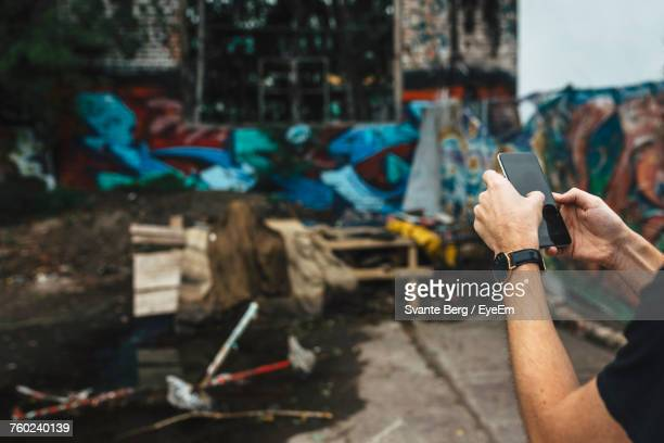 Cropped Hands Of Man Using Mobile Phone While Standing On Street