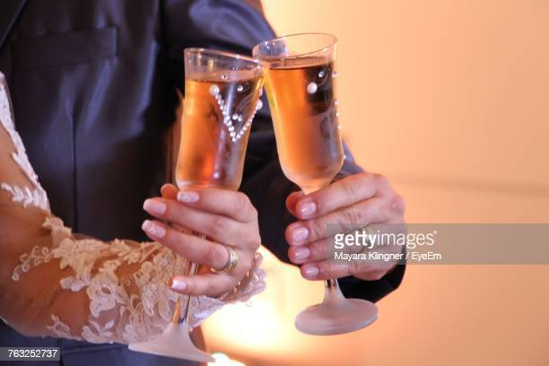 Cropped Hands Of Newlywed Couple Toasting Drinks At Ceremony