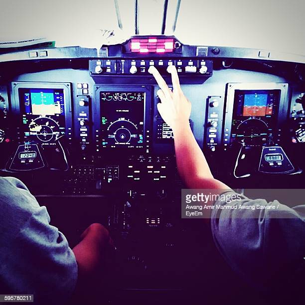 Cropped Hands Of Pilots At Cockpit Of Airplane
