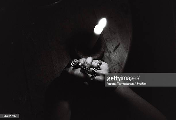 Cropped Hands Of Woman By Illuminated Candle On Table
