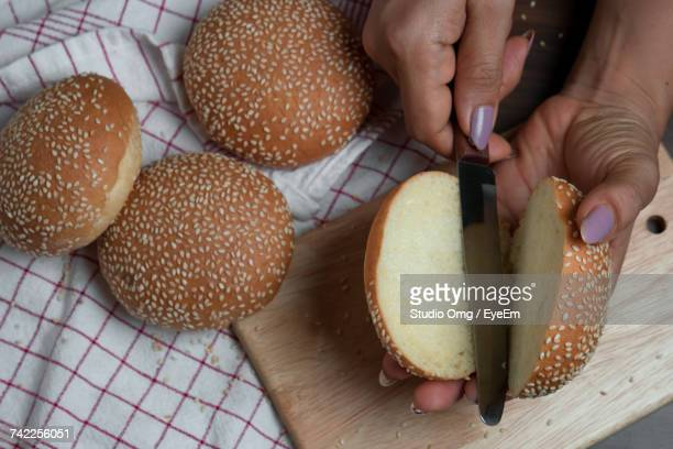 Cropped Hands Of Woman Cutting Sesame Seed Buns