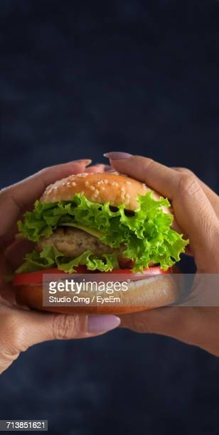 Cropped Hands Of Woman Holding Hamburger Against Black Background