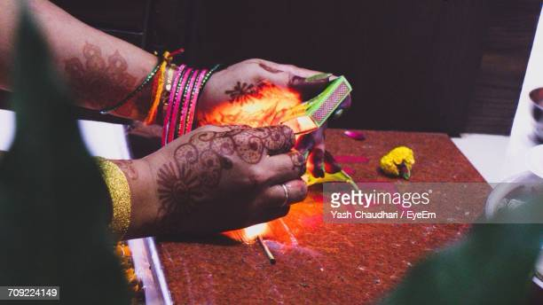Cropped Hands Of Woman Igniting Matchstick At Home
