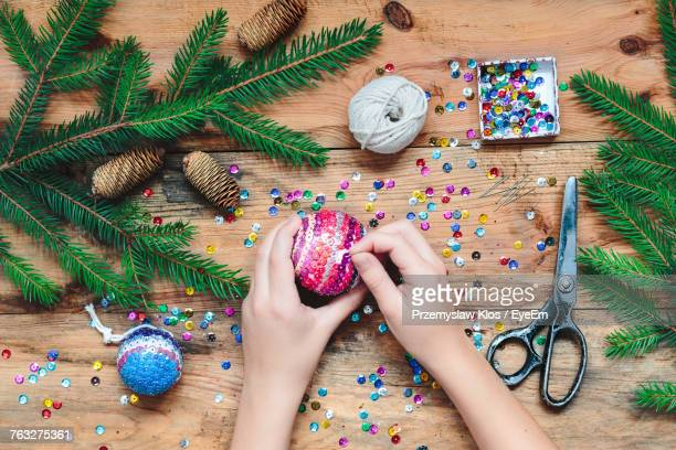 Cropped Hands Of Woman Making Christmas Decoration On Table