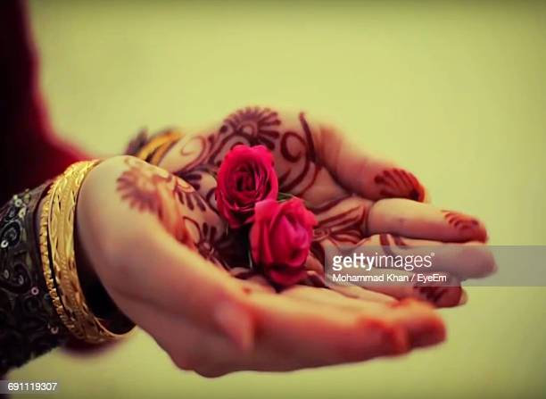 Cropped Hands Of Woman With Henna Tattoo And Pink Roses