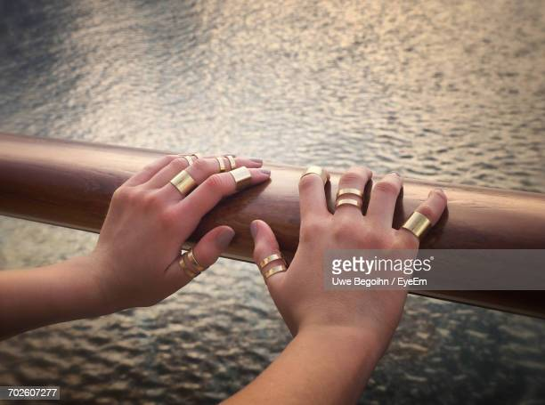 Cropped Hands On Woman On Railing Against Sea
