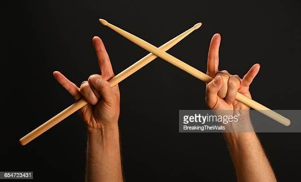 Cropped Hands With Rock Sign Holding Drumsticks Against Black Background