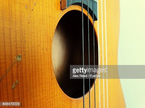 Cropped Image Of Acoustic Guitar Against White Background