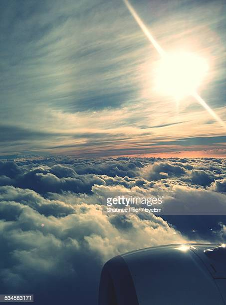 Cropped Image Of Airplane Flying Over Cloudscape