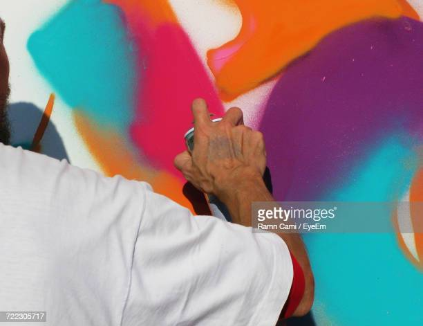 Cropped Image Of Artist Spray Painting On Wall