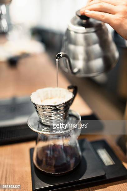 Cropped image of barista pouring boiling water in coffee filter at counter