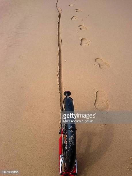 Cropped Image Of Bicycle By Footprints On Wet Sand At Beach