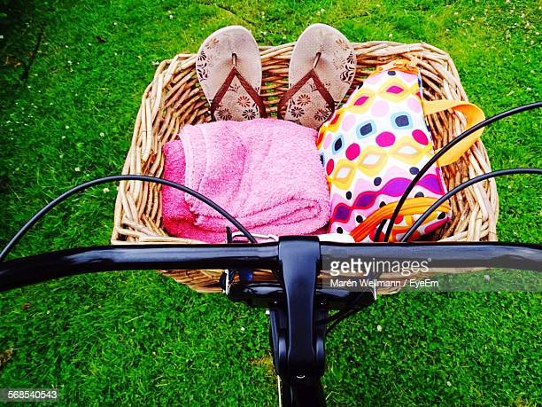 Cropped Image Of Bicycle Carrying Towel And Slippers On Grassy Field