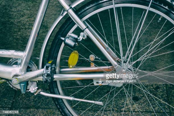 Cropped Image Of Bicycle Wheel By Wall