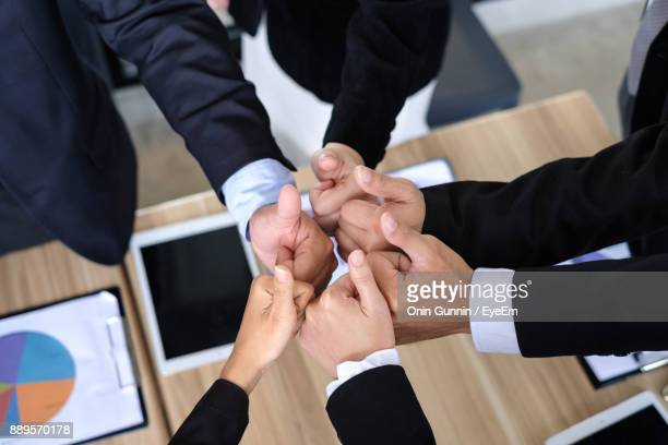 Cropped Image Of Business People Gesturing Thumbs Up At Office
