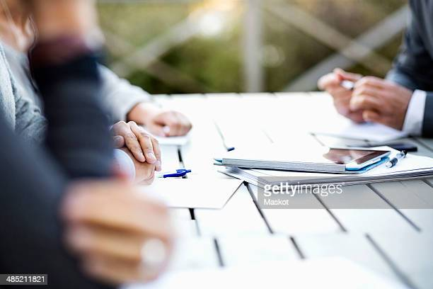 Cropped image of business people with documents and digital tablet at table