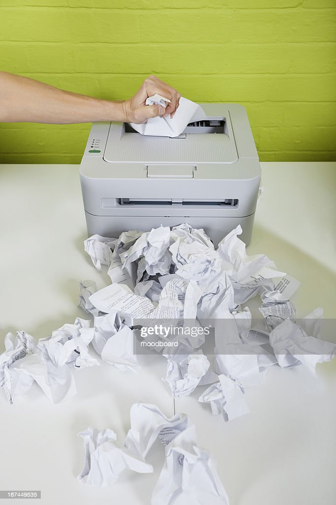 Cropped image of businessman's hand using printer with paper balls on desk