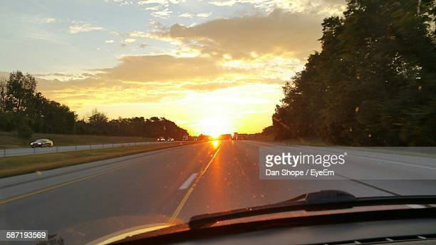 Cropped Image Of Car On Road Against Sky During Sunset