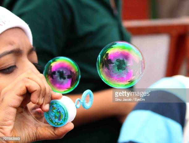 Cropped Image Of Child Blowing Bubble Wand