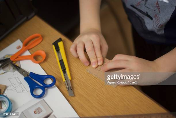 Cropped Image Of Child Hand With Work Tools And Paper At Table