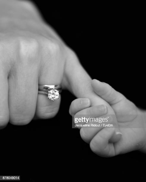 Cropped Image Of Child Holding Woman Hand Against Black Background