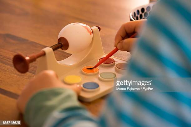 Cropped Image Of Child Painting Easter Egg At Table