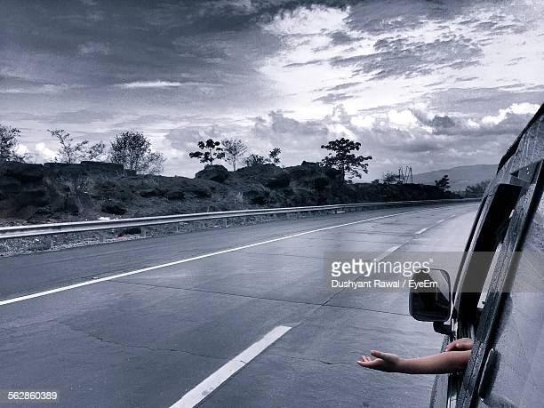Cropped Image Of Child Putting Hand Out Of Car Window During Rainy Season
