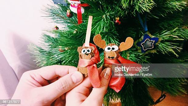 Cropped Image Of Couple Hand Holding Handmade Reindeer Against Christmas Tree