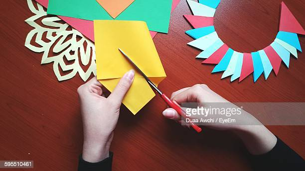 Cropped Image Of Craftsperson Cutting Yellow Paper