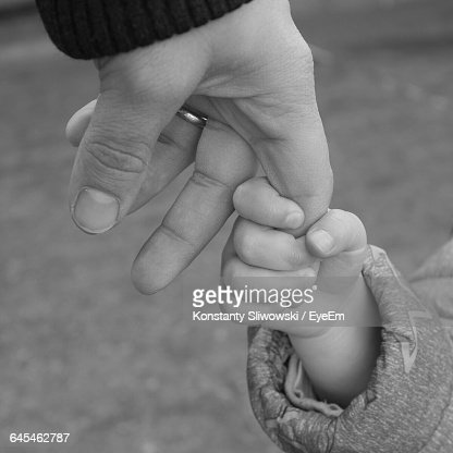 Cropped Image Of Daughter Holding Father Finger : Stock Photo