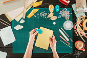 cropped image of designer stapling sheets of paper for scrapbooking postcard