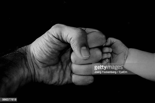 Cropped Image Of Father And Child Bumping Fist Against Black Background