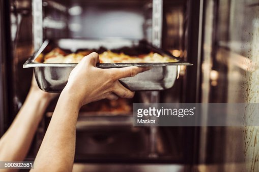 Cropped image of female chef putting dish in oven