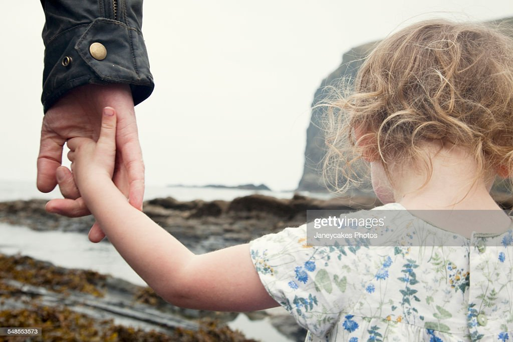 Cropped image of female toddler holding fathers hand whilst strolling on beach, Crackington Haven, Cornwall